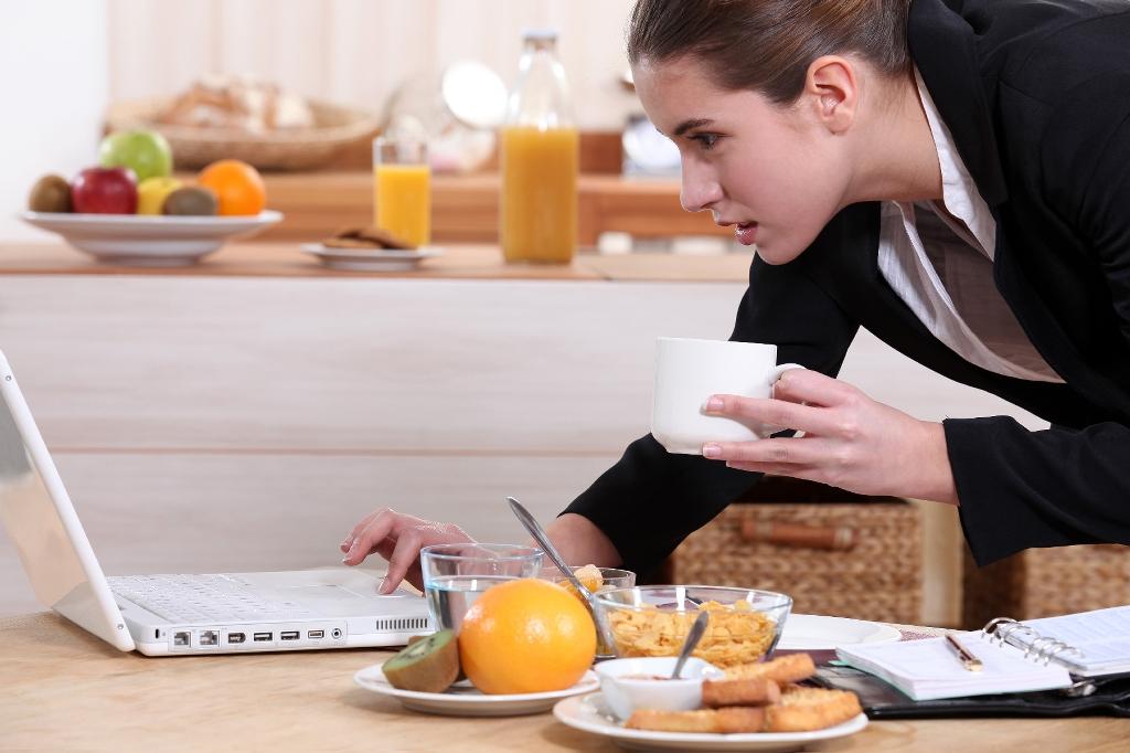 business-woman-on-laptop-eating-breakfast